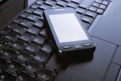 Telefono su un computer portatile Immagini Stock