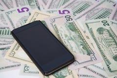 Telefono su un fondo di soldi Immagini Stock