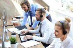 Telefonoperat?r som arbetar p? kollegan f?r v?sande ljud f?r call centerkontorsportion royaltyfri bild