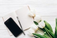 Telefonskärm- och anteckningsbokpenna och stilfulla tulpan på vitt trä arkivbild