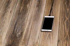 Telefonu komórkowego i ładowarki kabel czopował wewnątrz na drewnianym biurku Fotografia Royalty Free