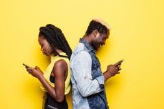 Telefonu nałóg Portret popierać młoda afro amerykańska para trwanie z powrotem używać telefony komórkowych odizolowywających nad  zdjęcie stock