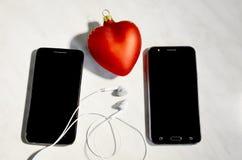 Telefony komórkowi, hełmofony i serce, Obrazy Stock