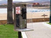 Telefonzelle auf dem Strand Stockbild