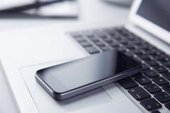 Telefoon die op een Laptop Computer rusten Stock Afbeelding