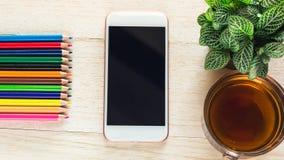 Telefoon en een kop thee op een houten lijst Kan geassembleerde advertentie zijn Royalty-vrije Stock Fotografie