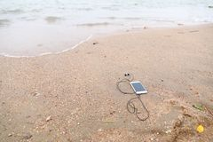 Telefoon en Hoofdtelefoon op het zandstrand royalty-vrije stock afbeelding