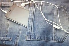 Telefoon en oortelefoon op jeans Stock Afbeeldingen