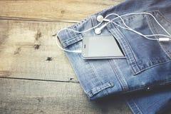 Telefoon en oortelefoon op jeans Royalty-vrije Stock Afbeelding