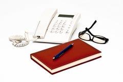 Telefoon, glazen, agenda, pen die op wit wordt geïsoleerdi Royalty-vrije Stock Afbeelding