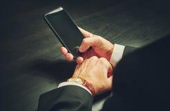 Telefoon in handen van een zakenman in dark Royalty-vrije Stock Fotografie