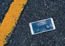 Telefoon met het gebroken scherm op asfalt Iemand gelaten vallen apparaat royalty-vrije stock afbeeldingen