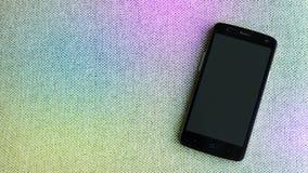 Telefoon op achtergrond van het oude materiaal dat van de zakregenboog wordt geïsoleerd Stock Afbeeldingen