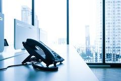Telefoon op bureau met de grote mening van de vensterstad Modern bureau stock afbeeldingen