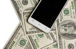 Telefoon op een achtergrond van geld Royalty-vrije Stock Afbeeldingen