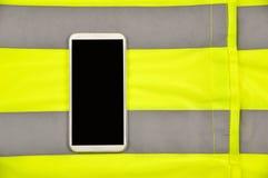 Telefoon over geel vest stock foto