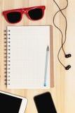 Telefoon, tablet, notitieboekje, hoofdtelefoons en zonnebril Royalty-vrije Stock Foto's