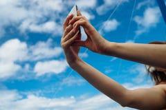Telefoon ter beschikking op blauwe hemel royalty-vrije stock afbeeldingen