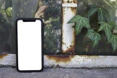 Telefoon ter beschikking op de achtergrond van bomen, park, tuin Lay-out voor de toepassing Telefoon met het wit scherm Het zwart royalty-vrije stock afbeeldingen