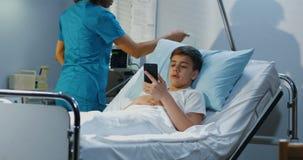 Telefoon van de tiener de geduldige gebruikende cel in het ziekenhuis stock videobeelden