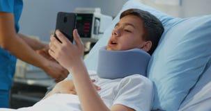 Telefoon van de tiener de geduldige gebruikende cel in het ziekenhuis stock footage