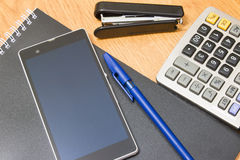 Telefoonachtergrond, calculator en nietmachine en pen op de lijst Stock Fotografie