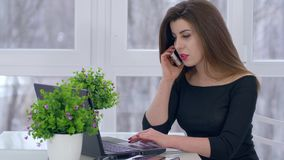 Telefoongesprek, jonge vrouw die op smartphone spreken en aan computerzitting bij lijst in ruimte werken stock footage