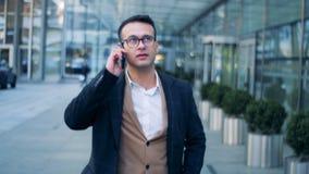 Telefoongesprek van een zakenman die in de stedelijke straat lopen, de stad in De rode epische lengte van de bioskoopcamera stock video