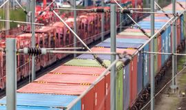 Telefotoaufnahme eines Frachtlastwagens auf den Schienen mit farbigen Behältern stockbild