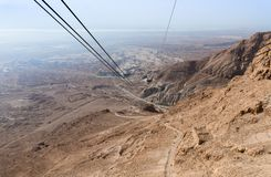 Telegrafíe el cable funicular que lleva a la estación más baja en el pie de la colina en la cual la fortaleza de Masada está situ imagenes de archivo