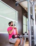Telegrafíe el entrenamiento del hombre de la máquina de la desconexión del lat en el gimnasio Imagen de archivo libre de regalías