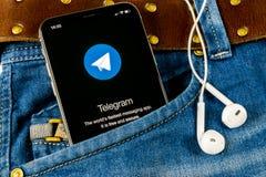 Telegram application icon on Apple iPhone X screen in jeans pocket. Telegram app icon. Telegram is an online social media network. Sankt-Petersburg, Russia stock photos