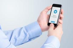 Telegrambudbärare på iPhoneskärm i manliga händer Arkivbilder