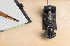 Telegraph key and notebook and pen Royalty Free Stock Image