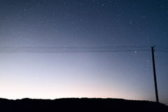Telegraph pole with wires against the night sky Royalty Free Stock Images