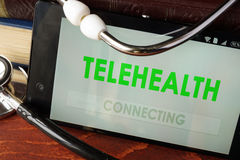 Telehealth apps open in a smartphone. And stethoscope Royalty Free Stock Photos