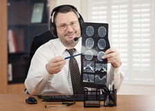 Telehealth doctor in headset reviewing brain scan images. Middle-aged male doctor with headset and glasses goes over brain x-rays results to virtual patient Stock Image
