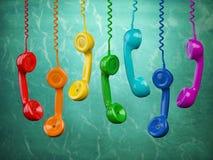 Telehone mottagare av olika färger som tillbaka hänger på gräsplanen Arkivbild