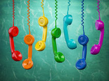 Telehone receivers of different colors hanging on the green back Stock Photography