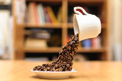 Telekinetic floating cup pouring coffee beans Royalty Free Stock Photography