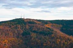 Telekommunikation ragt auf den Gipfel des Hügels hoch, der mit buntem Fallwald bedeckt wird Lizenzfreie Stockbilder