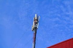 Telekommunikation ragt gegen blauen Fr?hlingshimmel und -wolken hoch stockfotografie