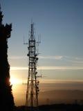 Telekommunikationantenn på solnedgången Royaltyfria Bilder