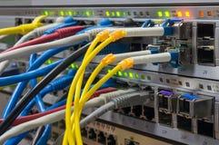 Telekommunikationer rack med strömbrytare och kulöra UTP och fiber Arkivfoton