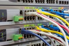 Telekommunikationsgestell mit Schaltern und farbigen Verbindungskabeln Stockbilder