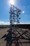 Telekommunikationsturm mit Mikrowelle, Radioantennen und Satellitenschüsseln mit Schatten auf dem Dach Lizenzfreies Stockfoto