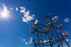 Telekommunikationsturm mit Mikrowelle, Radioantennen und Satellitenschüsseln mit Schatten auf dem Dach Stockfoto