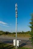 Telekommunikationsturm mit zwei Kästen mit Computerausrüstung und Straße im Hintergrund Lizenzfreies Stockfoto