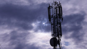 Telekommunikationtorn med moln och solen i bakgrund Arkivfoto
