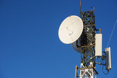 Telekommunikationtorn på soluppgång och blå himmel Arkivbilder